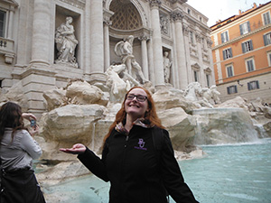Emily Long smiling in front of the famous Trevi Fountain in Italy