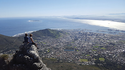 Phil Sedgwick sitting at the edge of a cliff with a friend, overlooking the city and the sea