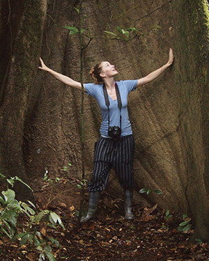 Zoe Compton standing in front of a huge tree in the amazon
